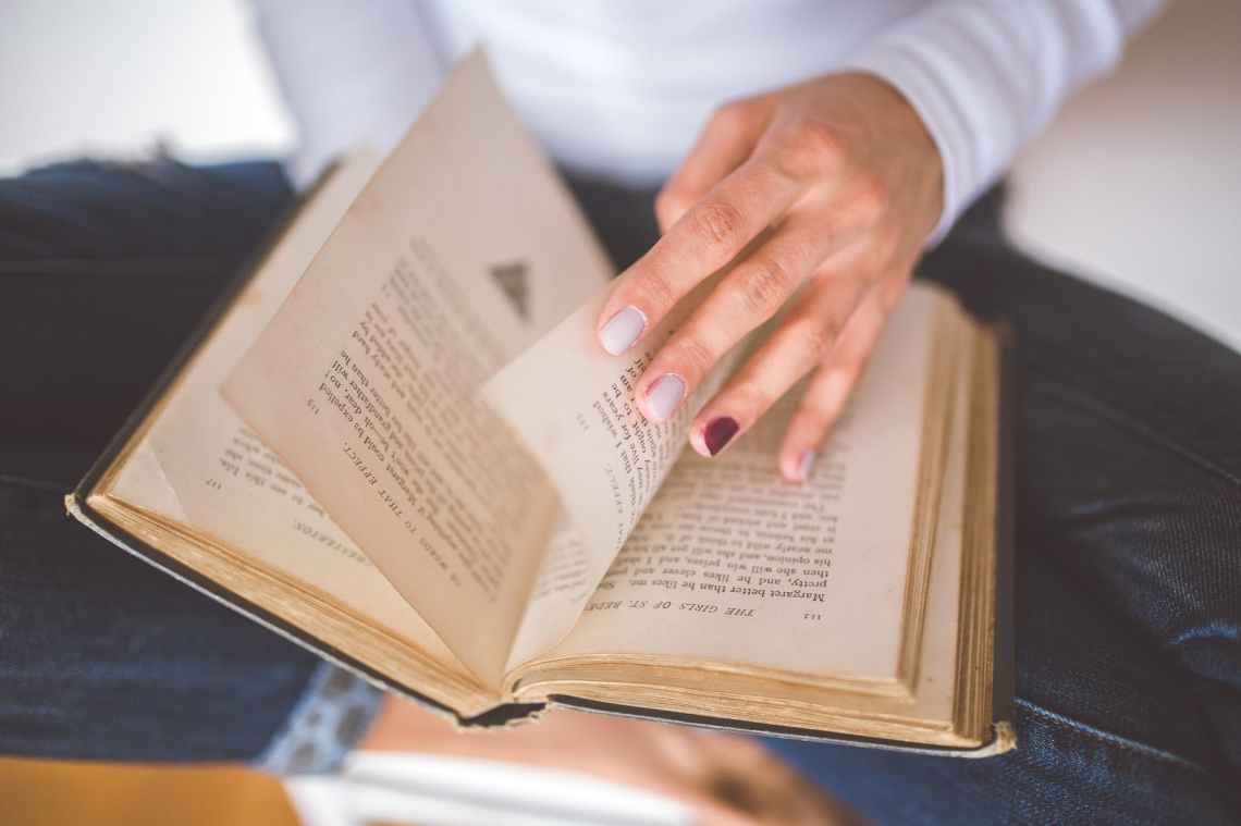 girl thumbs through the old book